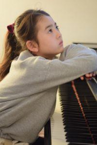 ピアノの前で上を見上げる女子