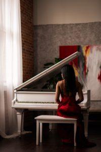 白ピアノと赤ドレスの女性