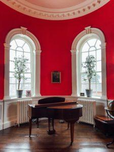 赤い壁と茶ピアノ